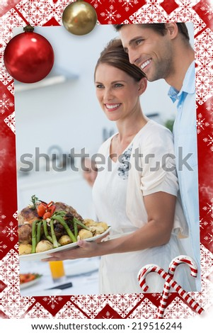 Cheerful couple showing roast chicken in the kitchen against christmas themed page - stock photo