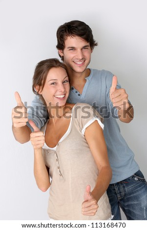 Cheerful couple showing thumbs up, isolated - stock photo