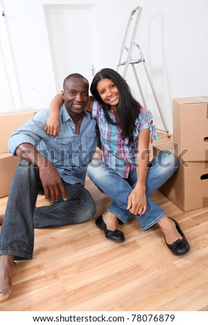 Cheerful couple sitting in empty new house - stock photo