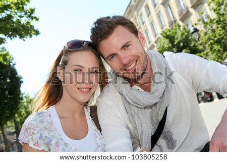 Cheerful couple sitting on a public bench in town - stock photo