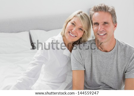 Cheerful couple sitting on bed smiling at camera