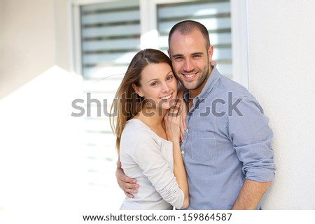 Cheerful couple standing in front of home