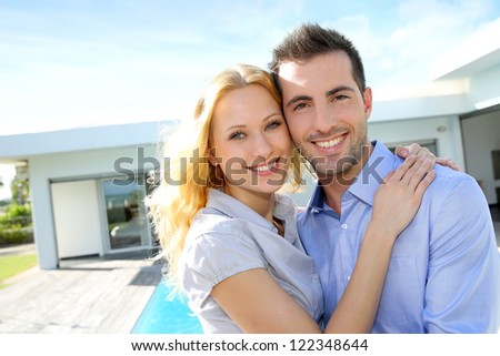 Cheerful couple standing in front of modern house - stock photo
