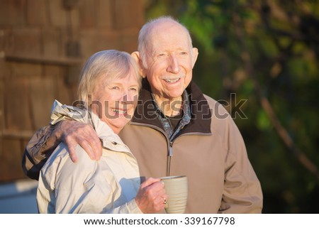Cheerful couple standing outdoors with coffee mug - stock photo