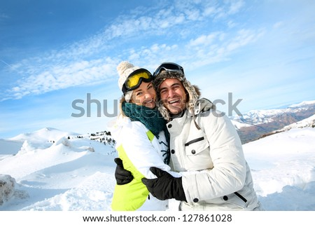 Cheerful couple standong on mountain peak