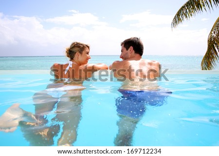 Cheerful couple swimming in infinity pool - stock photo