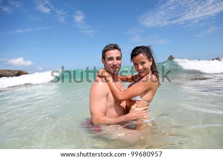Cheerful couple swimming in the ocean