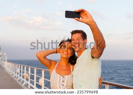 cheerful couple taking photo of themselves on cruise ship - stock photo