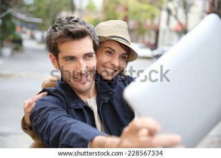Cheerful couple taking picture with tablet