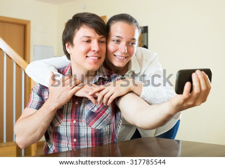 Cheerful couple taking selfie with a smartphone
