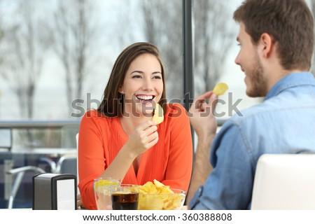 Cheerful couple talking and eating chip potatoes looking each other dating inside a coffee shop with an exterior background - stock photo