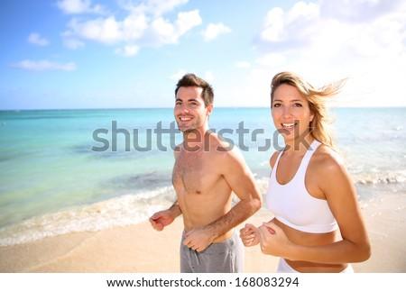 Cheerful couple training on the beach - stock photo