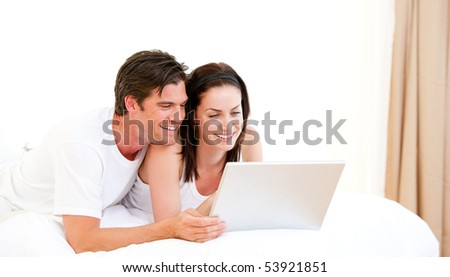 Cheerful couple using a computer lying on their bed at home