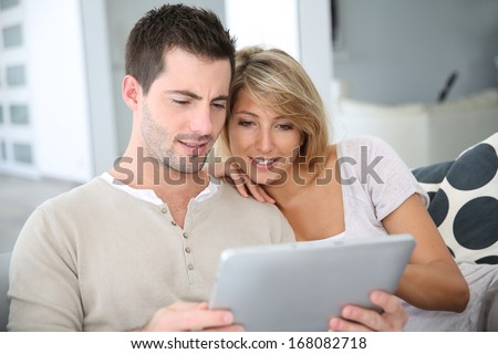 Cheerful couple using digital tablet at home - stock photo