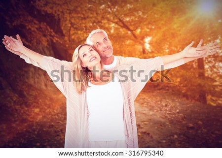 Cheerful couple with arms outstretched against autumn scene - stock photo