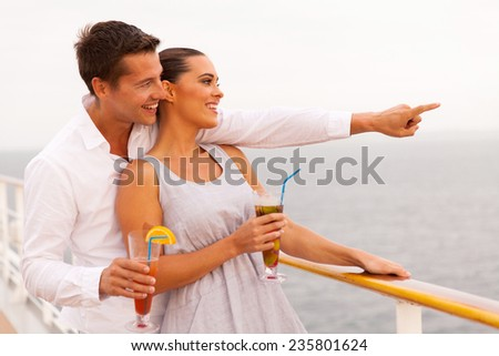 cheerful couple with cocktails enjoying sea view from cruise ship - stock photo