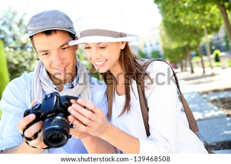 Cheerful couple with photo camera in touristic area - stock photo