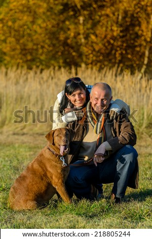 Cheerful couple with retriever dog in autumn park sunset - stock photo