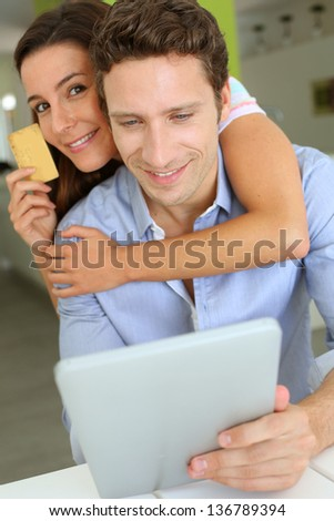 Cheerful couple with tablet shopping on internet - stock photo