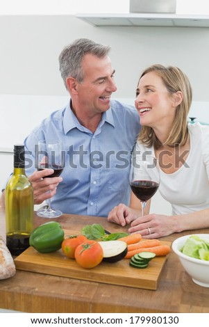 Cheerful couple with wine glasses in the kitchen at home