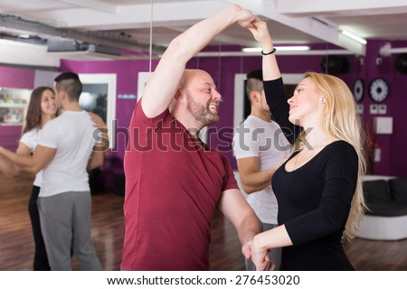 Cheerful couples enjoying of partner dance indoor