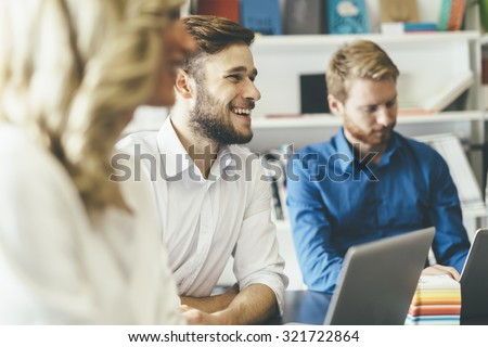 Cheerful coworkers in office during company meeting - stock photo