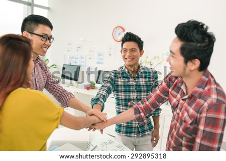 Cheerful coworkers with hands in stack: successful teamwork concept