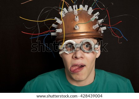 Cheerful crazy inventor helmet for brain research - stock photo