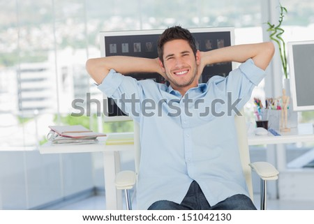 Cheerful creative business employee resting on his swivel chair - stock photo