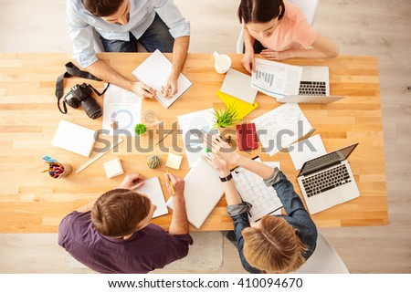 Cheerful creative team is discussing a project - stock photo