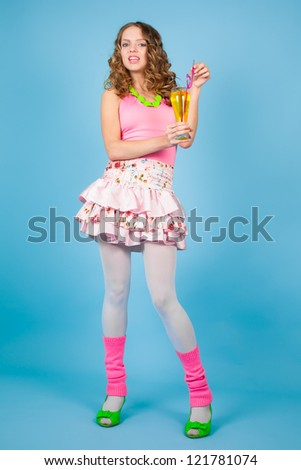 Cheerful curly-haired woman with cocktail on the blue background - stock photo