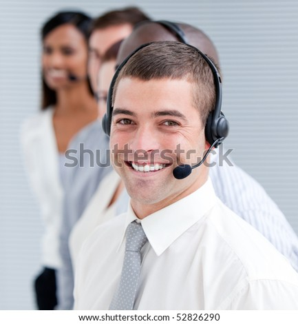Cheerful customer service representatives with headset on standing in a line