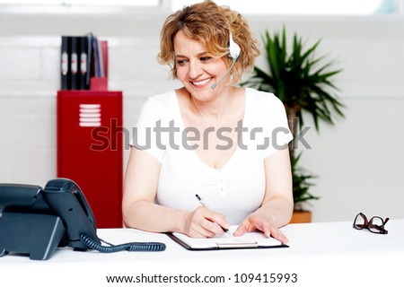 Cheerful customer support executive at work writing down customer complaints