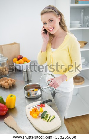 Cheerful cute blonde phoning and making dinner in bright kitchen - stock photo