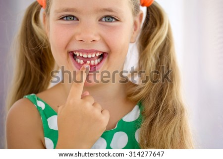Cheerful cute girl with teeth dropped out