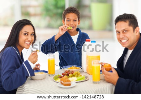 cheerful cute indian family enjoying their breakfast together - stock photo