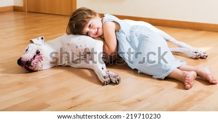 Cheerful cute little girl hugging big white dog lying on the floor at home