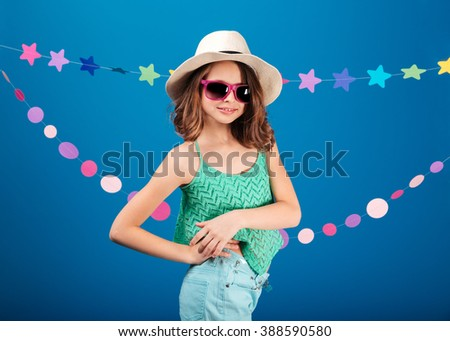 Cheerful cute little girl in sunglasses standing and posing over blue background  - stock photo