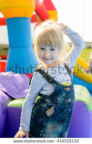 Cheerful cute little girl with blond hair standing on end in blue jean skirt dancing next to inflatable castle and slide outdoors - stock photo