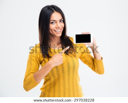Cheerful cute woman pointing finger on smartphone screen isolated on a white background. Looking at camera - stock photo