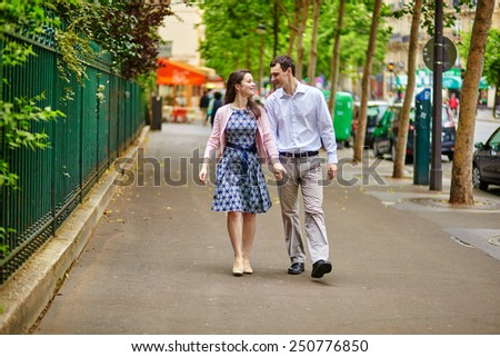 Cheerful dating couple is walking in Paris - stock photo