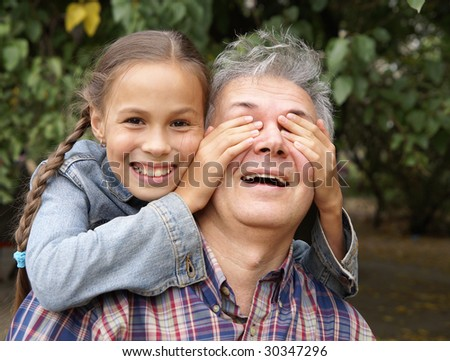 Cheerful daughter surprising her father - stock photo
