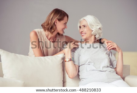 Cheerful delighted mother and her adult daughter resting at home