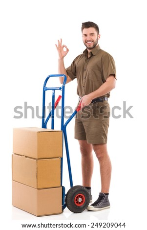 Cheerful delivery man standing with a push cart and showing ok sign. Full length studio shot isolated on white. - stock photo