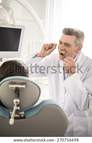 Cheerful dentist teaching his female patient how right to brush teeth with dental floss.