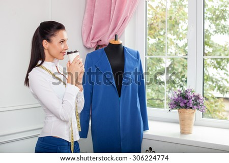 Cheerful designer of clothes is drinking coffee with pleasure. She is looking through a window dreamingly and smiling. The woman is standing near a mannequin of self-made clothing - stock photo