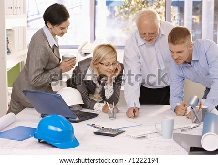 Cheerful designer team at work, senior architect taking notes on clipboard, colleagues watching, smiling.? - stock photo