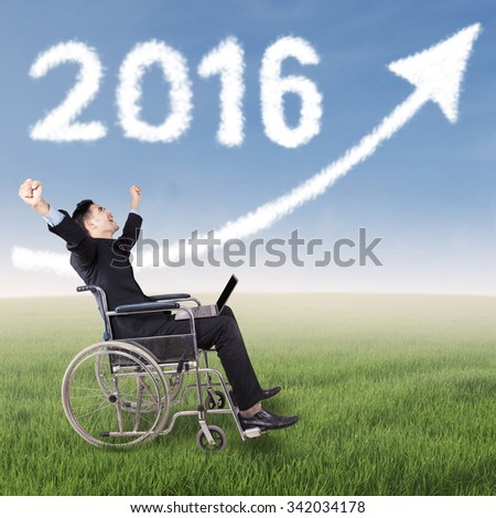 Cheerful disabled businessman expressing his success at field while sitting on wheelchair with clouds shaped numbers 2016 and arrow - stock photo