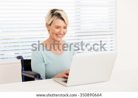 cheerful disabled senior woman using laptop on wheelchair at home - stock photo