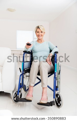 cheerful disabled senior woman watching television in living room